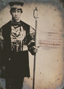 """A young Iowan Wide Awake in full uniform demonstrates for the 1860 Republican candidates Abraham Lincoln (for president), Hannibal Hamlin (for vice president), and Samuel R. Curtis (for congressman). His stern expression reflects the dire, militaristic seriousness that often replaced exuberant hoopla in the Wide Awake ranks. Reprinted from """"'The Prairies A-Blaze': Iowa Wide-Awakes Carry Torches for Lincoln,"""" Iowa Heritage Illustrated, 77 (Spring 1996). Courtesy Floyd and Marion Rinhart Collection, The Ohio State University Libraries."""